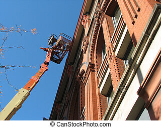 Historic Restoration - Men working from a lift bucket on a...