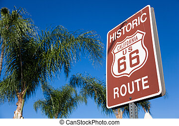 Historic route 66 highway sign with palm tree and a blue sky