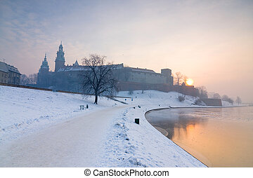 Historic royal Wawel Castle in Cracow, Poland, with frozen Vistula river in winter.