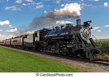 historic steam train passes through the fields