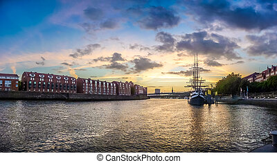 Historic town of Bremen with Weser river with dramatic clouds at sunset, Germany