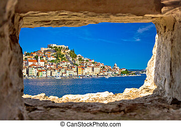 Historic town of Sibenik waterfront view through stone window