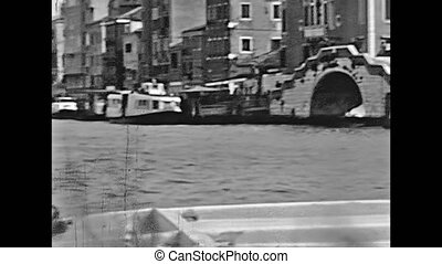 Historical boat tour on Fondamenta Nuove canal, person view of venetian lagoon and St. Francis church bell tower of Venice in Italy. Italian city of Unesco Heritage. Historical restored 1960 footage.