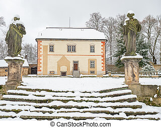 Historical building in winter garden. Old statues guard old stony staircase