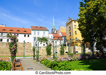 Historical buildings in city center with Cathedral of St. Bartholomew photographed from adjacent green park in Krizikovy sady, Pilsen, Czech Republic. Plzen, Western Bohemia.
