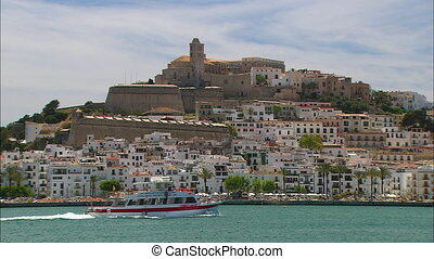 Medium low-angle still shot of beautiful white apartment buildings on a historical greek hilly island. At the hilltop is a historical museum with wind towers. A passenger ship sails along the island sea, Ibiza Balearic , Spain