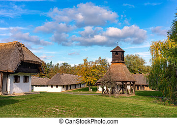 Historical old hungarian village with straw roof houses a bell tower