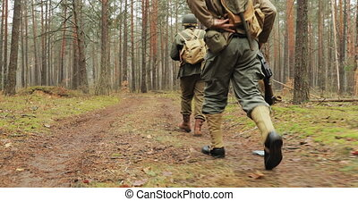 Historical Re-enactment. Re-enactors Dressed As American Soldiers Of USA Infantry Of World War II Marching Walking Along Forest Road In Autumn Day. Group of Soldiers Marching In Forest