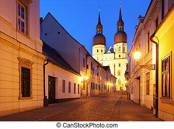 Historical street in Trnava with Saint Nicolas church...