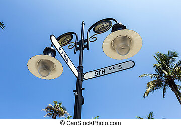 historical street sign in Naples, Florida under blue sky