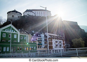 Historical town scape with Kufstein Fortress on a hillside and traditional houses, Austria.
