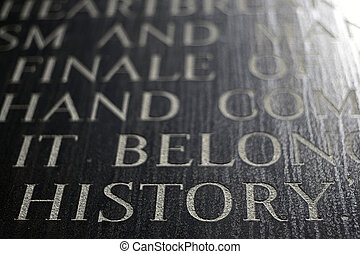 A closeup of the word HISTORY engraved on a war memorial.