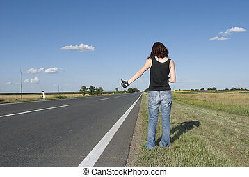 Young girl hitch hiking side a road