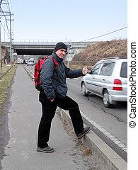 Hitch-hiker - Hitch-hiking on the roadside.