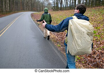 Hitch Hikers - Two men hitch hiking on an overcast rainy...