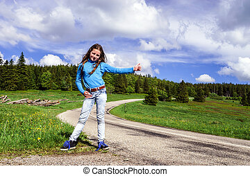 Hitch-hiking by young teenage girl on the road, Alsace