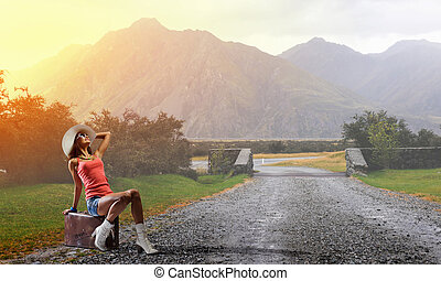 Hitch hiking traveling - Young retro woman waiting on road...