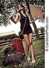 Hitch hiking - Young woman with a lot of luggage, trying to...