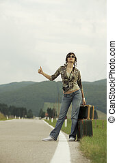 Hitchhiker - A woman hitchhikes on the side of the road.