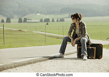 Hitchhiker - girl in the road sit atop vintage suitcase
