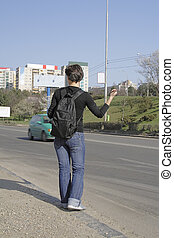 Hitchhiker girl waiting for a car on a road-side.