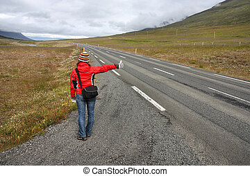 Hitchhiker in Iceland - girl traveler by the roadside. ...