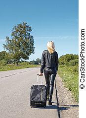 Hitchhiker walking along a rural road