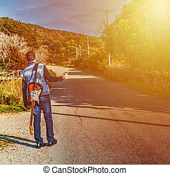 Hitchhiker with a guitar on the edge of the road at sunset