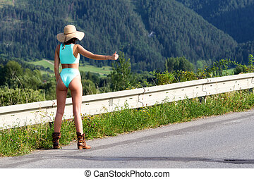Hitchhiking girl on road