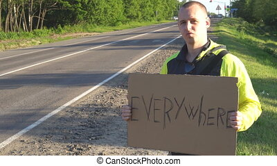 Hitchhiking traveling young adult man displaying Everywhere written sign board pointing thumb up on interstate highway