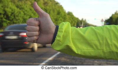 Hitchhiking traveling young adult man pointing thumb up on interstate highway