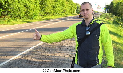 Hitchhiking traveling young adult man pointing thumb up on...