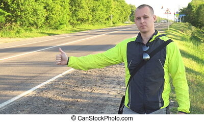 Hitchhiking traveling young adult man displaying Everywhere written sign board pointing thumb up on interstate highway.