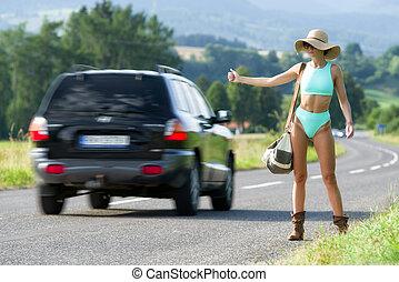 Hitchhiking young woman in bikini and sunhat on empty road