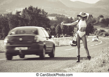 Hitchhiking young woman in bikin