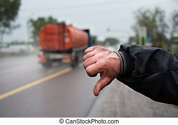 A male hand hitching a lift and a motorway with truck in the blurred background