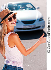 Hitching a ride. Beautiful young funky woman hitch-hiking on the side of the road and smiling with a car on background
