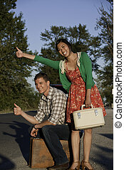 Hitching a ride young couple - Young man and asian girl with...
