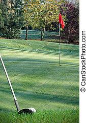 hitting golf ball onto green with club