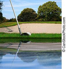 hitting golf ball over bunker
