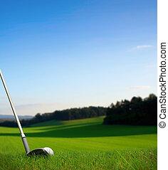 hitting golf ball with club towards green