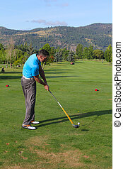 Hitting - Young male golfer hitting his tee-shot with driver