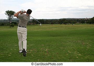 Hitting the bal - Player hitting a golf ball down the...