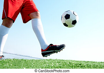 Horizontal image of soccer ball being kicked by footballer against blue sky