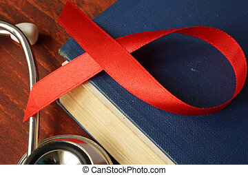HIV AIDS diagnosis. Awareness red ribbon on a book.