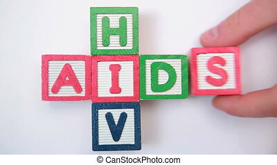 HIV and aids spelled out in blocks and then taken away by mans hand