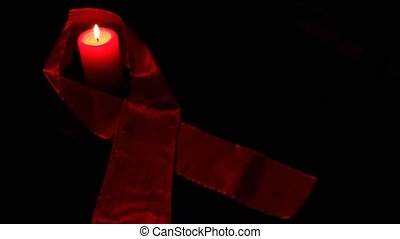 Awareness of HIV; red candle and ribbon.