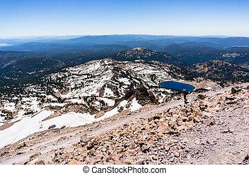 Hking on the trail to Lassen Peak; Lake Helen in the background; Lassen Volcanic National Park, California