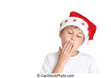 Ho Ho Hum - Tired boy wearing santa hat yawns