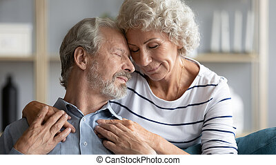 Hoary wife hugs from behind snuggle to beloved husband